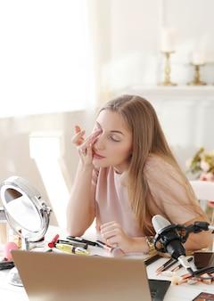 뷰티 동영상 블로거. 메이크업 자습서를 기록하는 젊은 여자
