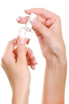 La mano femminile wellgroomed di bellezza tiene la bottiglia di un chiodo svanire sopra