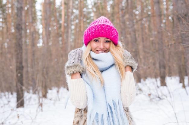 美しさ、冬、人々のコンセプト-雪に覆われた森のピンクのセーターの魅力的なブロンドの女性は