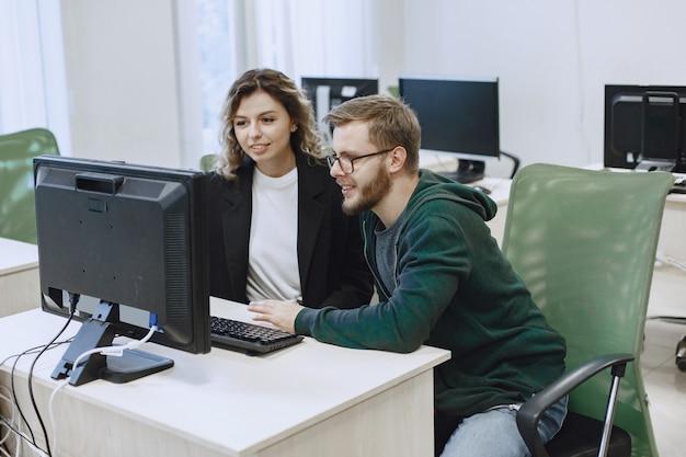 Красавица с другом. мужчина и женщина общаются. студенты изучают информатику.