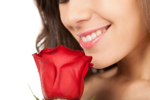 バラの美しさ。顔の近くに赤いバラを保持し、白い背景で隔離しながら笑顔の美しい若い女性のトリミングされた画像