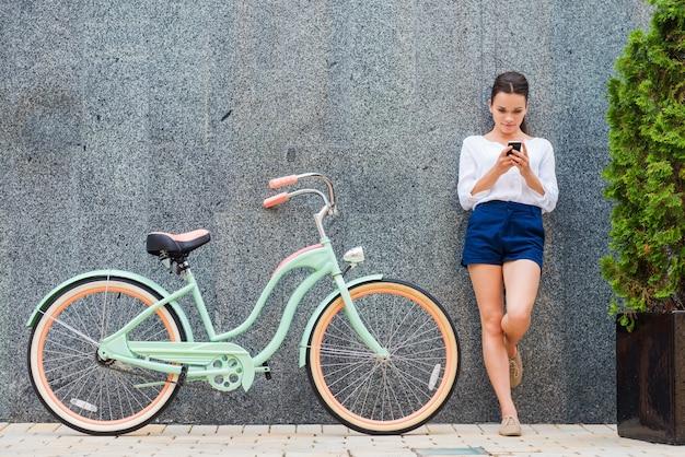 빈티지 자전거와 아름다움입니다. 거리에서 그녀의 빈티지 자전거 근처에 서 있는 아름 다운 젊은 웃는 여자