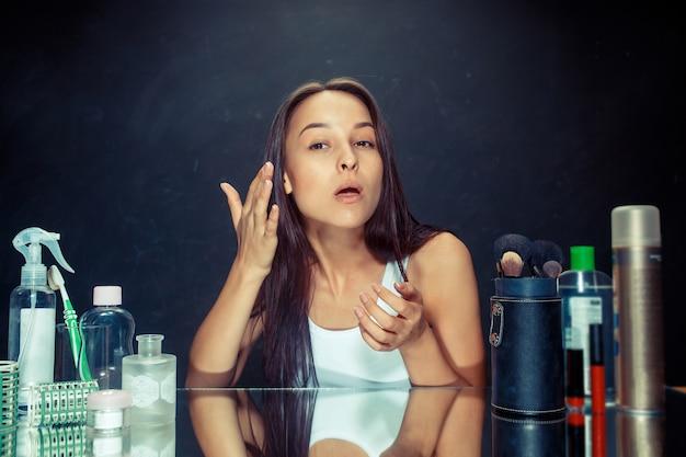 Женщина красоты после нанесения макияжа. красивая девушка смотрит в зеркало