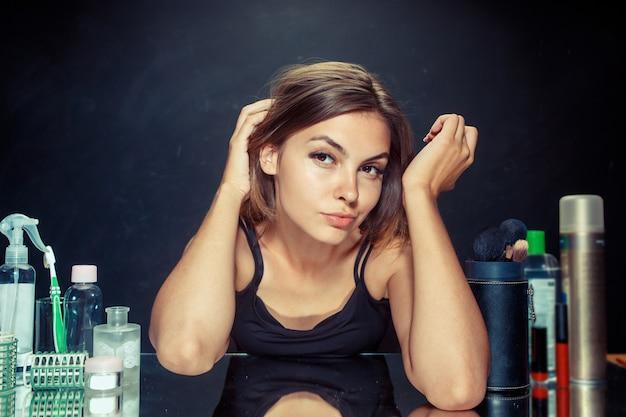 메이크업을 적용한 후 뷰티 우먼입니다. 거울을보고 아름 다운 소녀입니다. 아침, 메이크업 및 인간의 감정 개념. 스튜디오에서 백인 모델