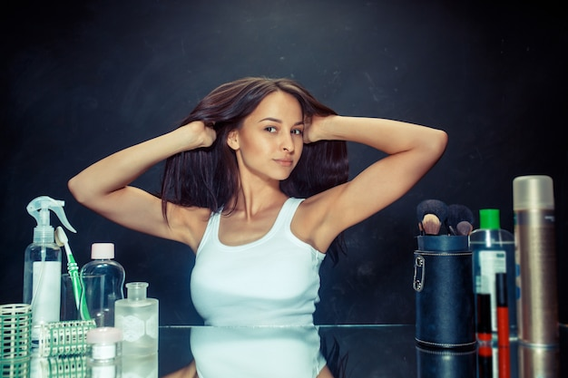 Женщина красоты после нанесения макияжа. красивая девушка смотрит в зеркало. утро, макияж и концепция человеческих эмоций. кавказская модель в студии