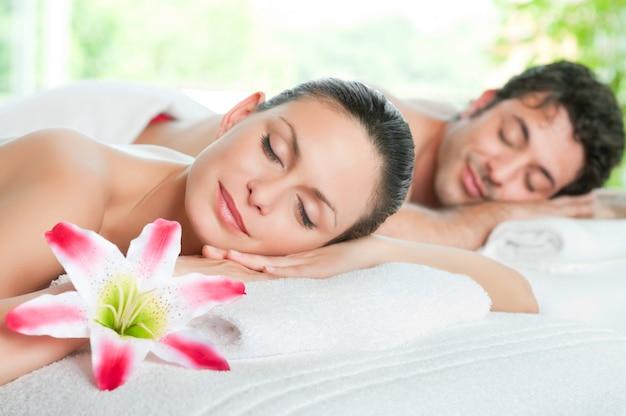 Женщина красоты и мужчина расслабляются вместе во время спа-процедуры