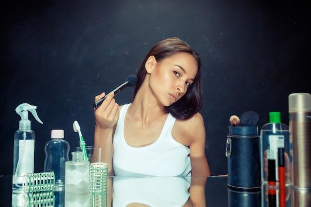 Женщина красоты, применяя макияж. красивая девушка смотрит в зеркало и наносит косметику большой кистью