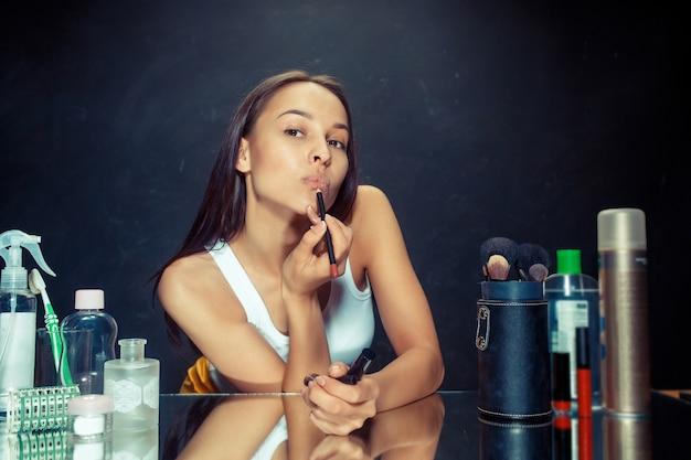 메이크업을 적용하는 뷰티 우먼. 거울을보고 브러시로 입술에 화장품을 적용하는 아름 다운 소녀. 아침, 메이크업 및 인간의 감정 개념. 스튜디오에서 백인 모델