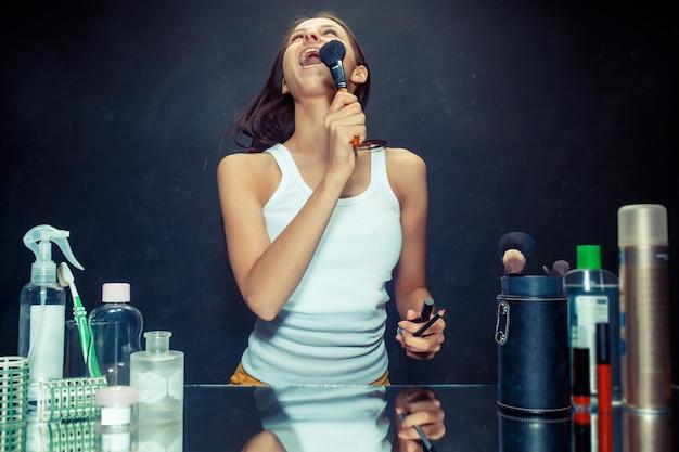 메이크업을 적용하는 뷰티 우먼. 거울을보고 큰 브러시로 화장품을 적용하는 아름 다운 소녀. 스튜디오 노래 노래에서 백인 모델