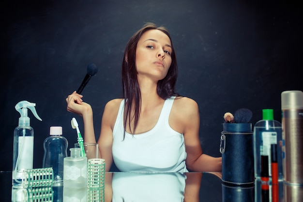 Женщина красоты, применяя макияж. красивая девушка смотрит в зеркало и наносит косметику с большой кистью. кавказская модель в студии