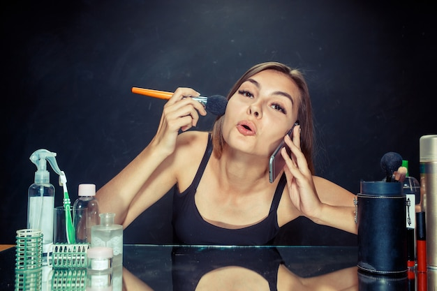 메이크업을 적용하는 뷰티 우먼. 거울을보고 큰 브러시로 화장품을 적용하는 아름 다운 소녀. 스튜디오에서 백인 모델