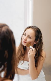Женщина красоты, применяя макияж. красивая девушка смотрит в зеркало и наносит косметику с большой кистью. девушка краснеет на скулах. пудра, румяна
