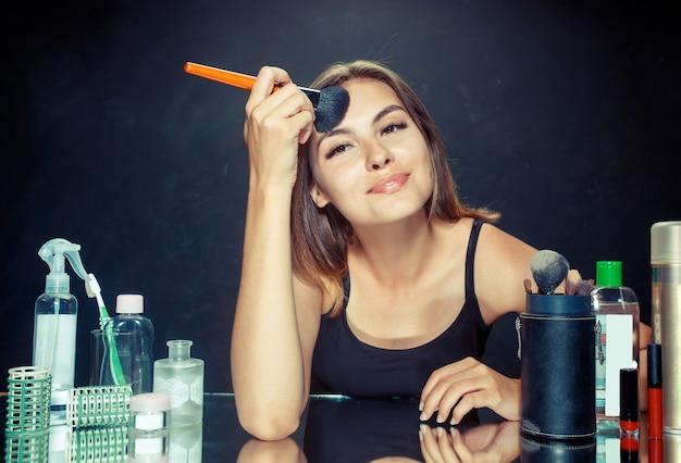 메이크업을 적용하는 뷰티 우먼. 거울을보고 큰 브러시로 화장품을 적용하는 아름 다운 소녀. 아침, 메이크업 및 인간의 감정 개념. 스튜디오에서 백인 모델