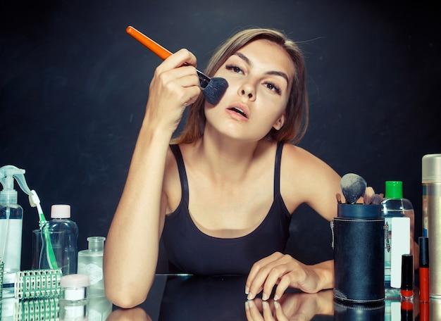Женщина красоты, применяя макияж. красивая девушка смотрит в зеркало и наносит косметику с большой кистью. утро, макияж и концепция человеческих эмоций.