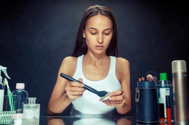 메이크업을 적용하는 뷰티 우먼. 거울을보고 큰 브러시로 화장품을 적용하는 아름 다운 소녀. 아침, 메이크업 및 인간의 감정 개념