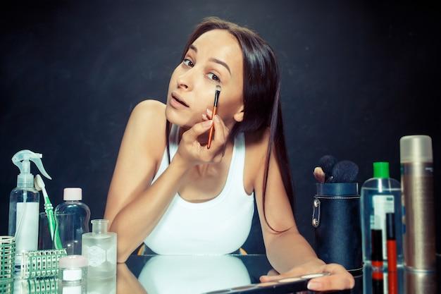 메이크업을 적용하는 뷰티 우먼. 거울을보고 브러시로 화장품을 적용하는 아름 다운 소녀. 아침, 메이크업 및 인간의 감정 개념. 스튜디오에서 백인 모델