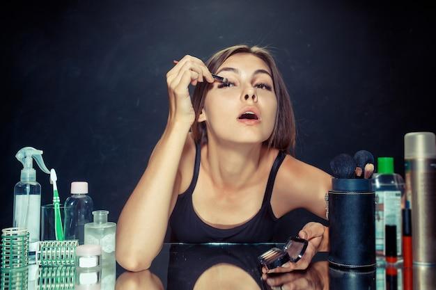 메이크업을 적용하는 뷰티 우먼. 거울을보고 브러시로 화장품을 적용하는 아름 다운 소녀. 아침, 메이크업 및 인간의 감정 개념