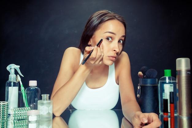 Женщина красоты, применяя макияж. красивая девушка смотрит в зеркало и наносит косметику с подводкой для глаз. утро, макияж и концепция человеческих эмоций. кавказская модель в студии
