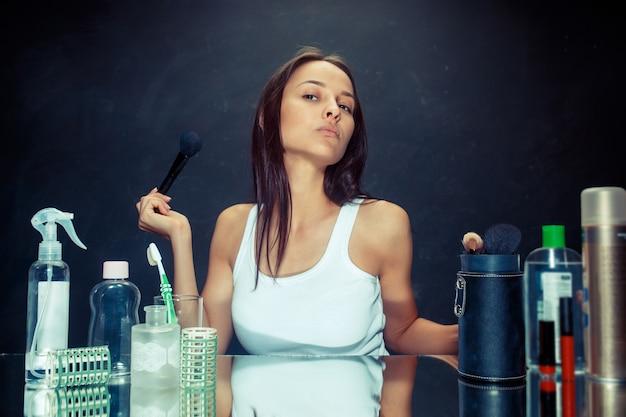 Donna di bellezza che applica trucco. bella ragazza guardarsi allo specchio e applicare cosmetici con un pennello grande. modello caucasico in studio