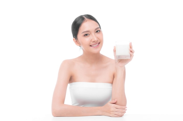 美容女性アジアのかわいい女の子は白い背景で朝の健康のためにミルクを飲んで幸せを感じる-ライフスタイル美容女性のコンセプト