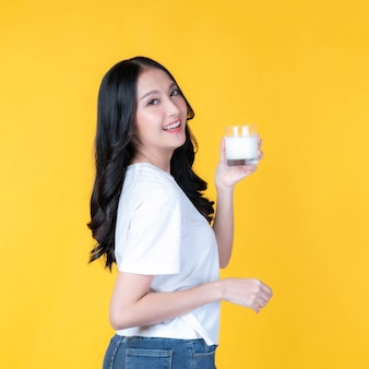 Beauty woman asian cute girl feel happy drinking milk for good health in the morning on yellow background - lifestyle beauty woman healthy concept