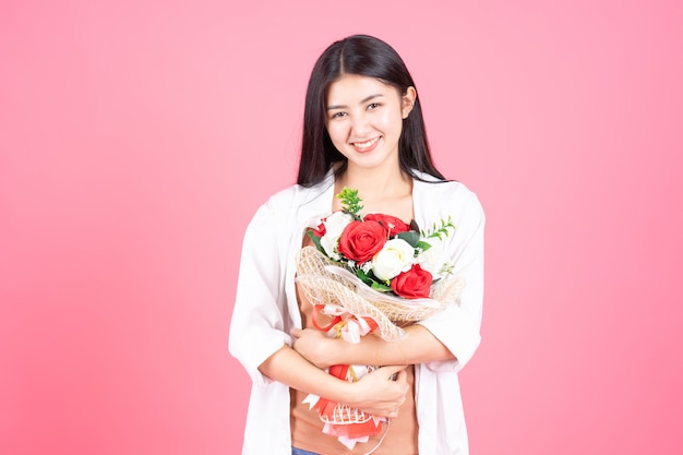 Beauty woman asian cute girl feel happy holding flower red rose and white rose on pink background