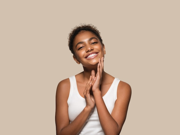 아름다움 여자 검은 피부 얼굴 웃는 모델 그녀의 얼굴을 만지고. 색상 배경입니다. 갈색