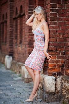 美容女性。ブロンドの女性が赤い建物の背景にポーズ