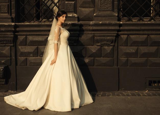 Красота женщины-невесты в белом удивительном свадебном платье и закат в городе
