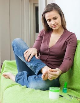 Женщина красоты, заботясь о ногтях на ногах