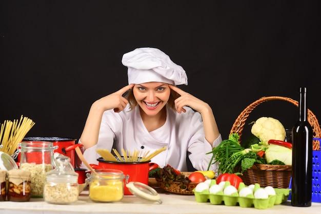 美人女性シェフ女性シェフと野菜の束陽気な魅力的な女性シェフが座っています