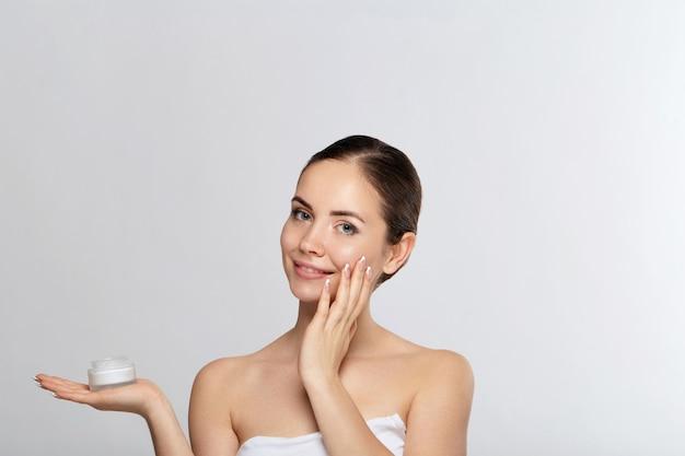뷰티 우먼 컨셉입니다. 피부 관리. 화장품 크림을 들고 부드러운 피부를 가진 젊은 모델. 보습 크림을 적용하고 자신의 얼굴을 터치하는 여성의 초상화. 피부 보호