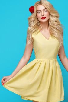 아름다움 여자 곱슬 금발 머리 꽃 머리 매니큐어 손톱. 트렌디한 색상은 파란색 노란색입니다. 스튜디오 촬영.