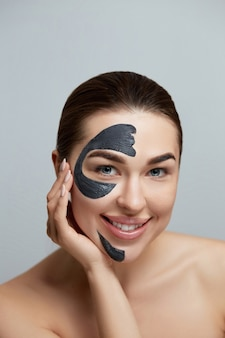 뷰티 여자 얼굴 마스크. 얼굴 피부 보습 마스크에 화장품 블랙 필링 마스크와 아름 다운 여자의 초상화. 피부 관리. 미용술