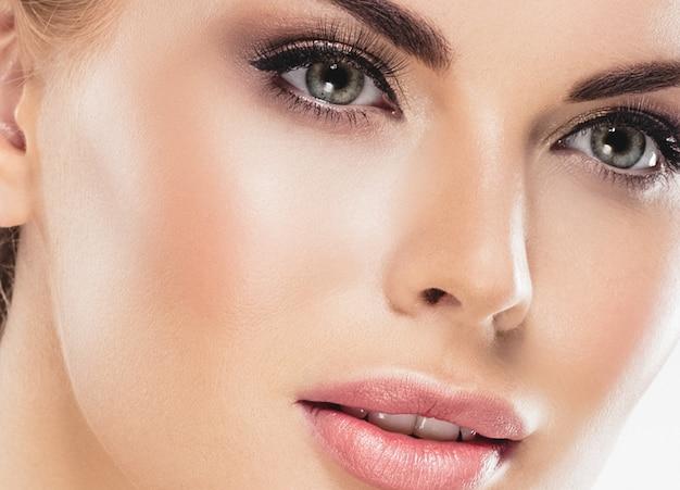 美女顔ポートレート。パーフェクトフレッシュクリーンスキンカラーリップパープルレッドの美しいモデルの女の子。ブロンドの髪の若者とスキンケアのコンセプト。白い背景で隔離。スタジオショット。