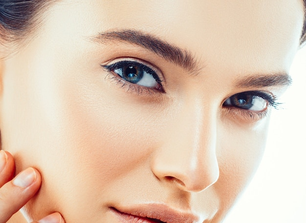 손으로 뷰티 우먼 얼굴입니다. 초상화. 완벽하고 신선한 깨끗한 피부를 가진 아름다운 스파 모델 소녀. 카메라를 보고 웃고 있는 여성. 젊음과 피부 관리 개념