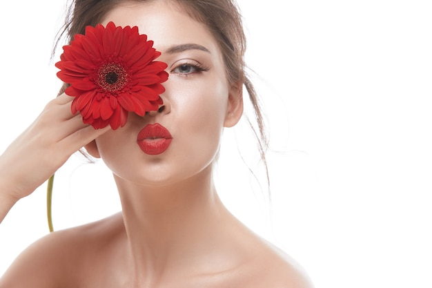 キスを送信し、彼女の目の近くに花を保持している赤い口紅で美女の顔