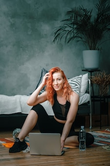 The beauty woman goes in for sports at home. cheerful sporty woman with red hair  sitting, smilling   and watching  in laptop, shootting  blog  in the bedroom