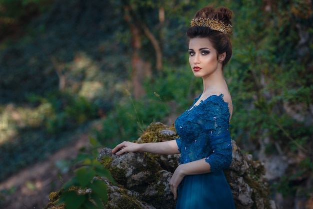 Beauty woman in green luxury expensive dress and in crown on the nature. beautiful model girl in a green wedding dress. female portrait in the park. woman with hairstyle. cute lady outdoors