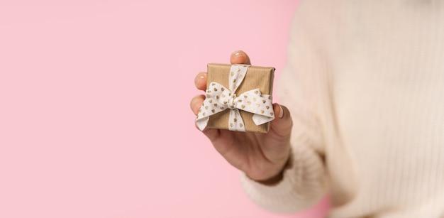 Руки женщины красоты держа подарочную коробку с лентой сердца на розовом фоне, крупным планом. пастельные тона