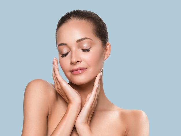 美容女健康肌清潔スパマニキュア爪手が顔に触れる。色の背景青