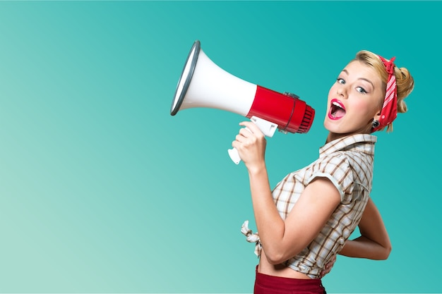 Beauty woman holding big megaphone, dressed in pin-up style with red lips on green background