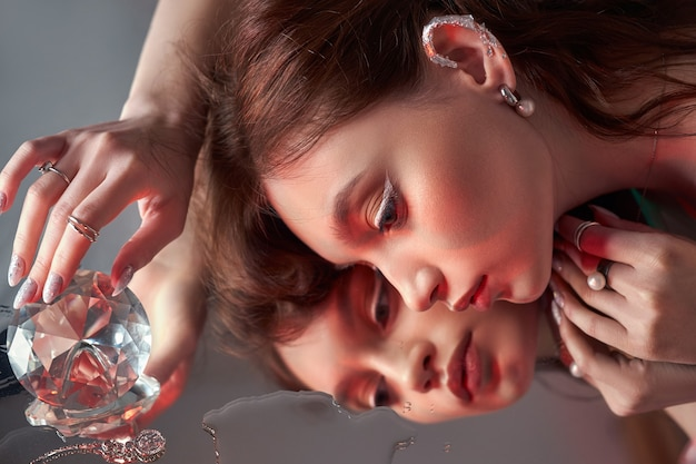 Beauty woman holds big diamond in hand while lying on table. beautiful hands, professional manicure, large brilliant