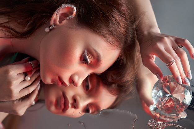 Beauty woman holds big diamond in hand while lying on table