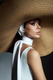 大きな籐の帽子と軽い夏のドレスの美女