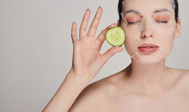 目と手で深刻な顔に新鮮なキュウリと保湿マスクの美しさの女性は彼女の顔の近くの両方の手でキュウリを保持