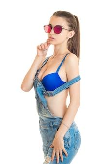 全体的にジーンズの美しさの女性と白い背景で隔離のサングラスとカメラを見て美しいシリコンブリーツと青いブラジャー
