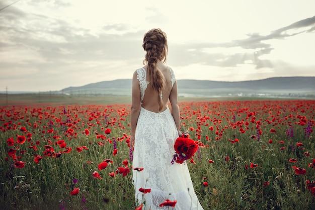 Женщина красоты в маковом поле в белом платье. красивая невеста в стиле бохо на закате в поле красных маков