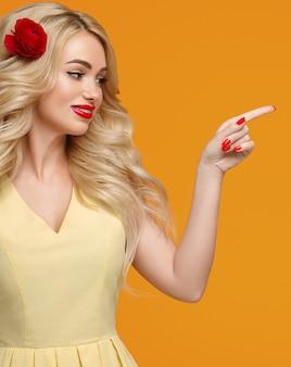 아름다움 여자 긴 곱슬 금발 머리 꽃 머리 잘 손질 된 손톱. 트렌디한 컬러 오렌지와 옐로우