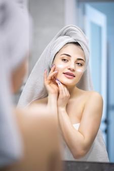 Donna di bellezza che si guarda allo specchio, applicando una crema idratante per lozione sulle guance, finendo la routine mattutina domestica per la cura della pelle